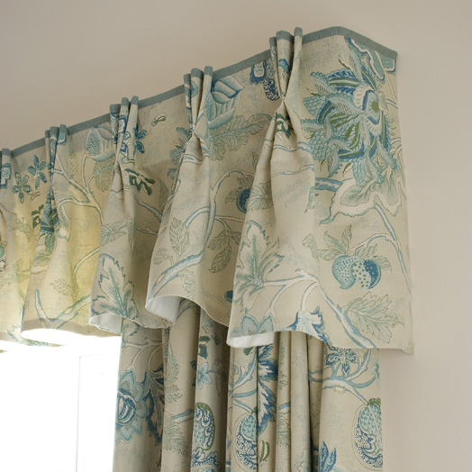 A shaped triple pleat valance with a contrast border on top edge